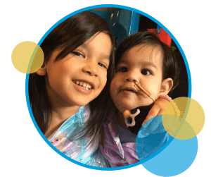 Two young children who are sisters cuddling. The younger one who is about two years old has a nasogastric tube.